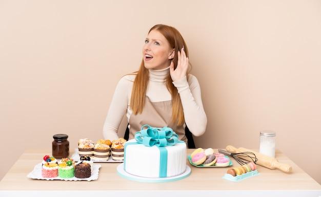 Jonge roodharigevrouw met een grote cake die iets luistert