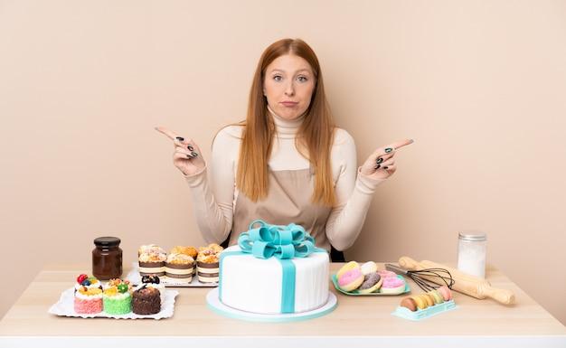 Jonge roodharigevrouw met een grote cake die naar de zijkanten wijzen die twijfels hebben