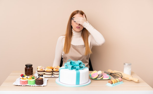 Jonge roodharigevrouw met een grote cake die ogen behandelen door handen