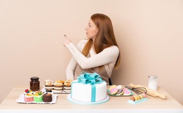 Jonge roodharigevrouw met een grote cake die terug met de wijsvinger richten
