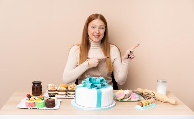 Jonge roodharigevrouw met een grote cake die vinger aan de kant richt