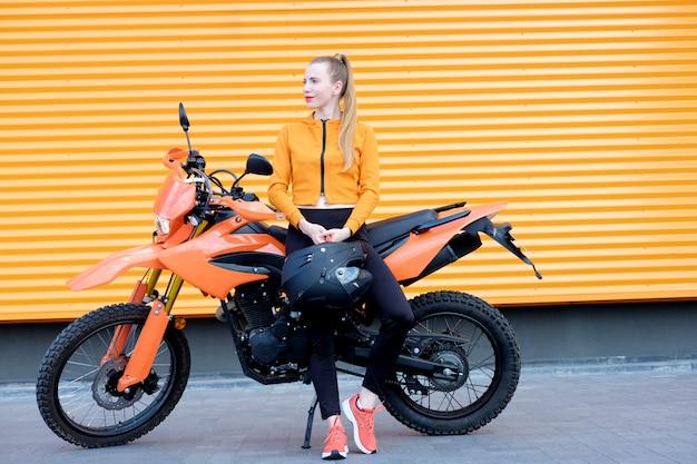 Jonge roodharigevrouw met oranje lippenstift gekleurde lippen