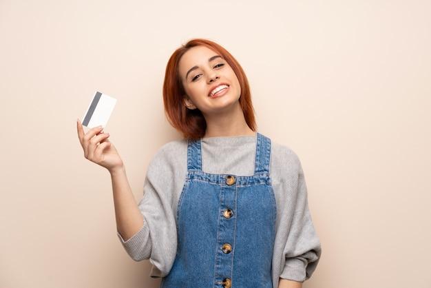 Jonge roodharigevrouw over geïsoleerde muur die een creditcard en het denken houden