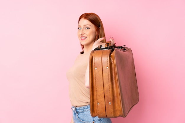 Jonge roodharigevrouw over geïsoleerde roze achtergrond die een uitstekende aktentas houdt