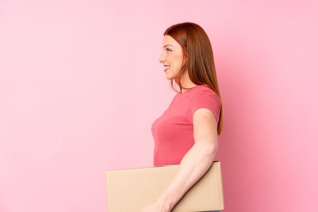 Jonge roodharigevrouw over geïsoleerde roze muur die een doos houdt om het naar een andere plaats in zijpositie te verplaatsen