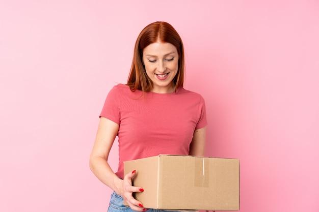 Jonge roodharigevrouw over geïsoleerde roze muur die een doos houdt om het naar een andere plaats te verplaatsen