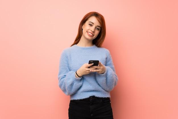 Jonge roodharigevrouw over roze die een bericht met mobiel verzenden