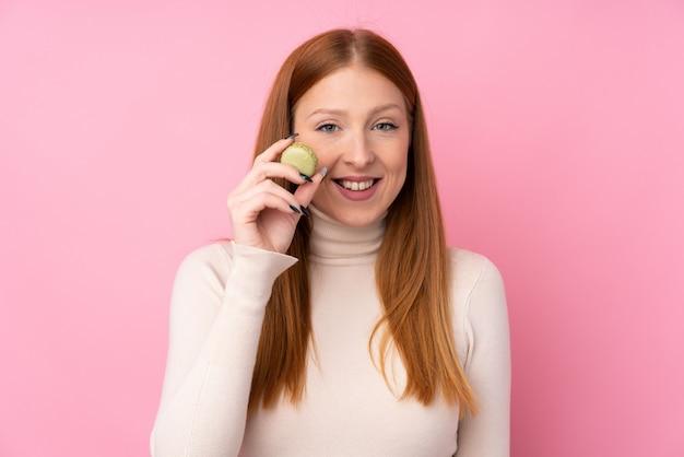 Jonge roodharigevrouw over roze die kleurrijke franse macarons houden