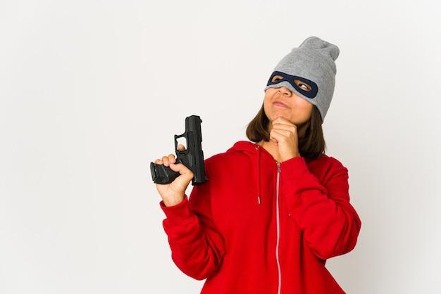 Jonge rover spaanse vrouw die een masker draagt dat zijwaarts met twijfelachtige en sceptische uitdrukking kijkt