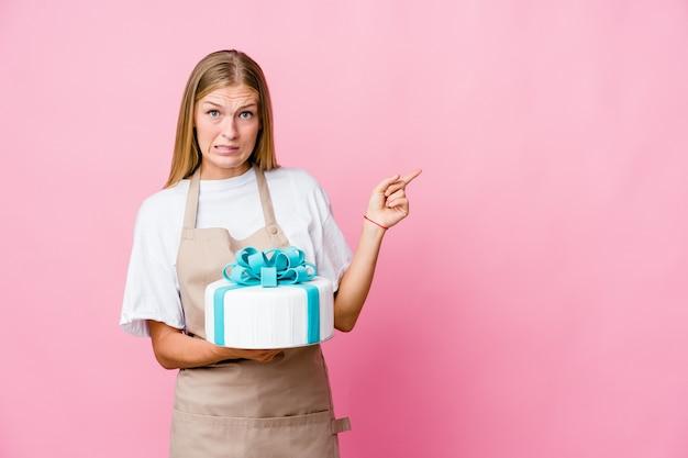 Jonge russische bakkersvrouw die een heerlijke cake houden geschokt wijzend met wijsvingers naar een exemplaarruimte