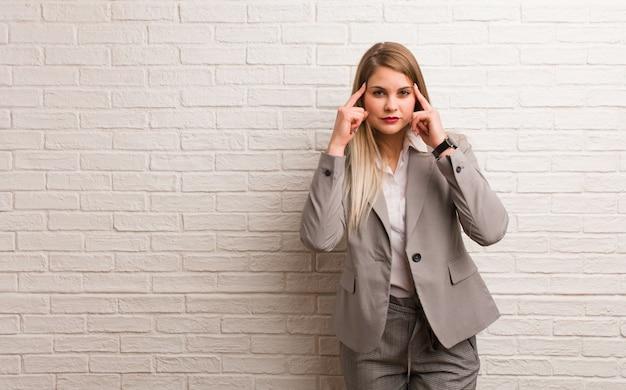 Jonge russische bedrijfsvrouw die een concentratiegebaar doet