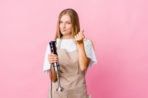 Jonge russische kokvrouw die een elektrische geïsoleerde mixer houdt die aantoont dat zij geen geld heeft.