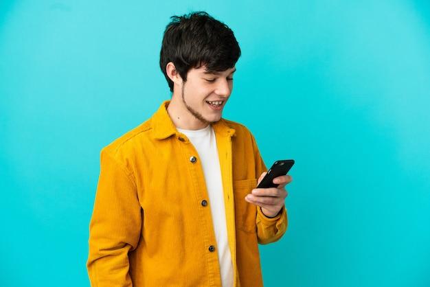 Jonge russische man geïsoleerd op blauwe achtergrond die een bericht of e-mail verzendt met de mobiel