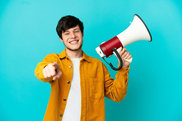 Jonge russische man geïsoleerd op blauwe achtergrond met een megafoon en glimlachend terwijl hij naar voren wijst