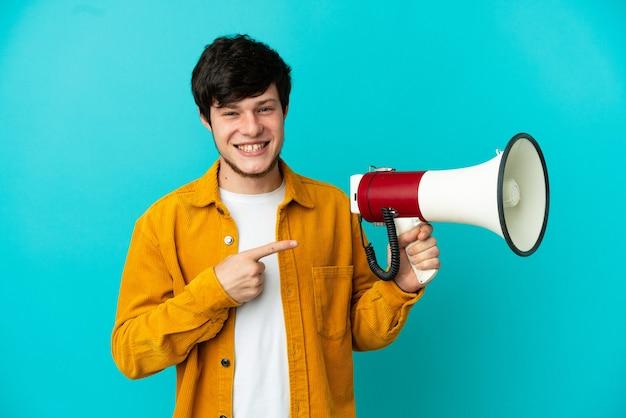 Jonge russische man geïsoleerd op blauwe achtergrond met een megafoon en wijzende kant
