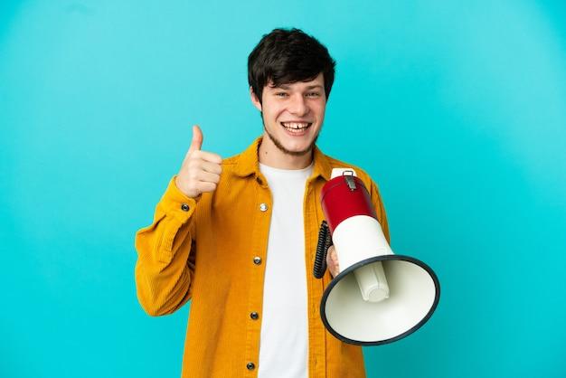 Jonge russische man geïsoleerd op blauwe achtergrond met een megafoon met duim omhoog
