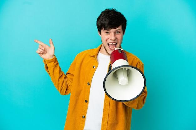 Jonge russische man geïsoleerd op blauwe achtergrond schreeuwen door een megafoon en wijzende kant