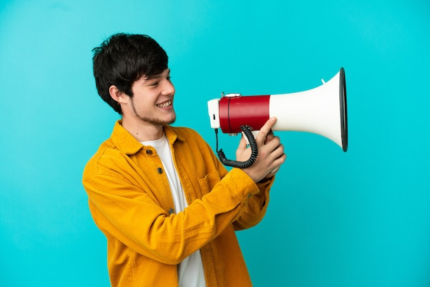 Jonge russische man geïsoleerd op blauwe achtergrond schreeuwen door een megafoon om iets aan te kondigen
