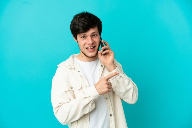 Jonge russische man met behulp van mobiele telefoon geïsoleerd op blauwe achtergrond wijzend naar de zijkant om een product te presenteren