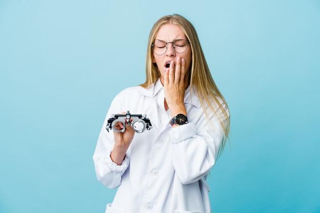 Jonge russische optometristvrouw op blauwe geeuw die een moe gebaar toont dat mond behandelt met hand