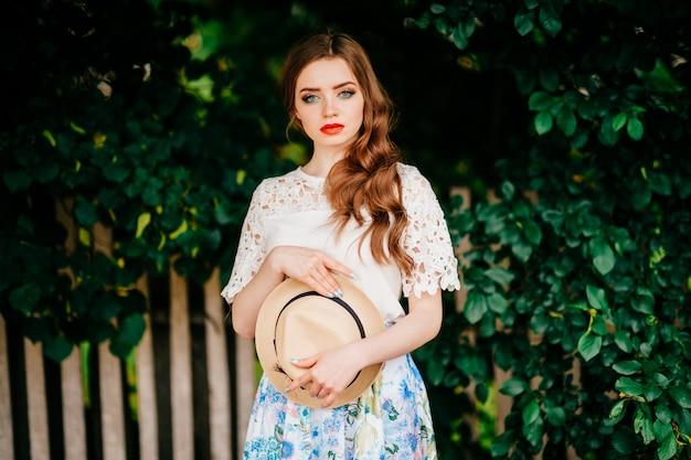 Jonge russische schoonheid. aantrekkelijk meisje in vintage retro lange rok, witte ouderwetse top en krullend rood haar en strohoed poseren voor camera met hek en groene bomen