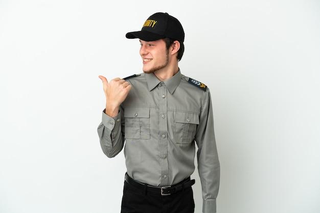 Jonge russische veiligheidsman geïsoleerd op een witte achtergrond die naar de zijkant wijst om een product te presenteren