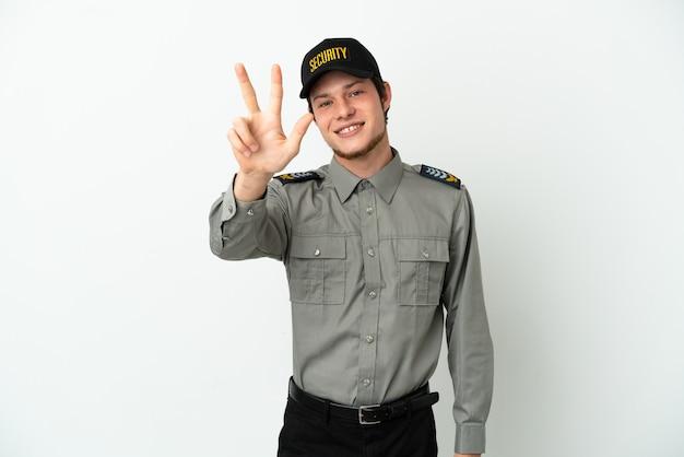 Jonge russische veiligheidsman geïsoleerd op een witte achtergrond gelukkig en drie tellen met vingers