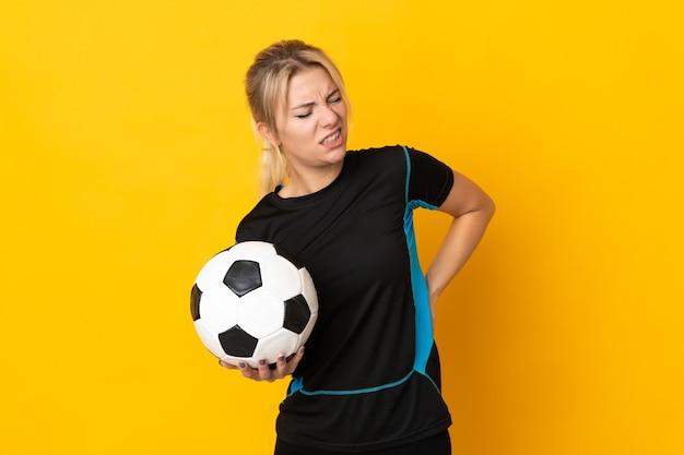 Jonge russische voetballervrouw die op gele achtergrond wordt geïsoleerd die aan rugpijn lijdt omdat zij zich heeft ingespannen