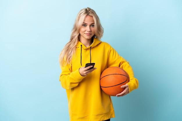 Jonge russische vrouw basketbal spelen geïsoleerd op blauw een bericht verzenden met de mobiel