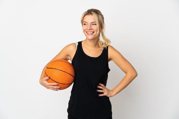 Jonge russische vrouw basketbal spelen geïsoleerd op een witte achtergrond poseren met armen op heup en glimlachen