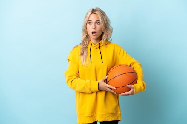 Jonge russische vrouw die basketbal speelt dat op blauw wordt geïsoleerd die verrassingsgebaar doet terwijl naar de kant kijkt