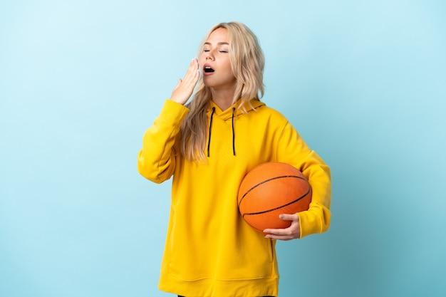 Jonge russische vrouw die basketbal speelt dat op blauwe muur wordt geïsoleerd die en wijd open mond behandelt met hand