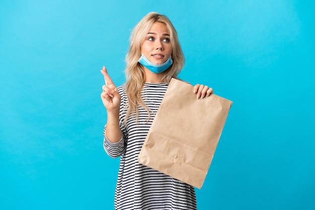 Jonge russische vrouw die een boodschappentas houdt die op blauw met vingers wordt geïsoleerd die en het beste wensen