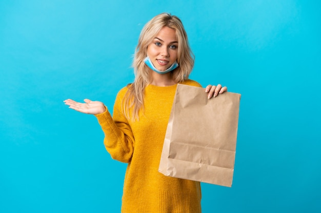 Jonge russische vrouw die een boodschappentas houdt die op blauw wordt geïsoleerd dat copyspace denkbeeldig op de palm houdt om een advertentie in te voegen