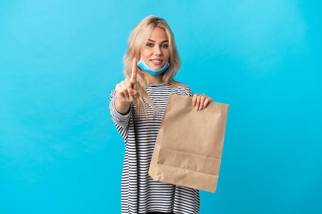 Jonge russische vrouw die een boodschappentas houdt die op blauw wordt geïsoleerdt en een vinger opheft