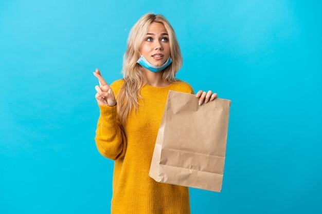 Jonge russische vrouw die een boodschappentas houdt die op blauwe achtergrond met vingers wordt geïsoleerd die en het beste wensen