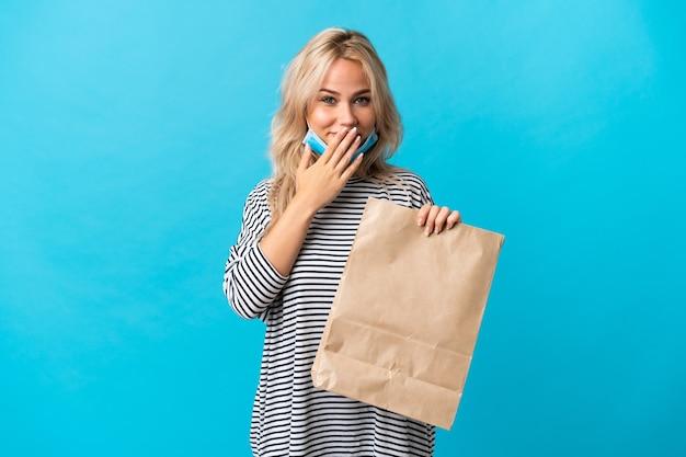 Jonge russische vrouw die een boodschappentas houdt die op blauwe achtergrond wordt geïsoleerd, gelukkig en glimlachend die mond met handen behandelen
