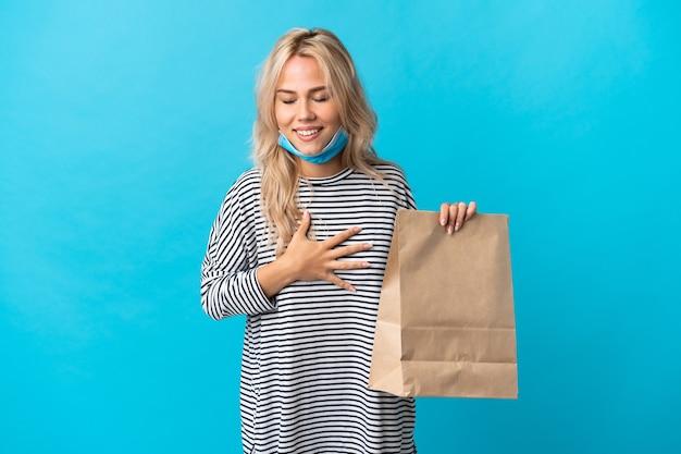 Jonge russische vrouw die een boodschappentas houdt die op blauwe muur wordt geïsoleerd die veel glimlacht