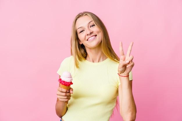 Jonge russische vrouw die een geïsoleerd roomijs eet die nummer twee met vingers toont.