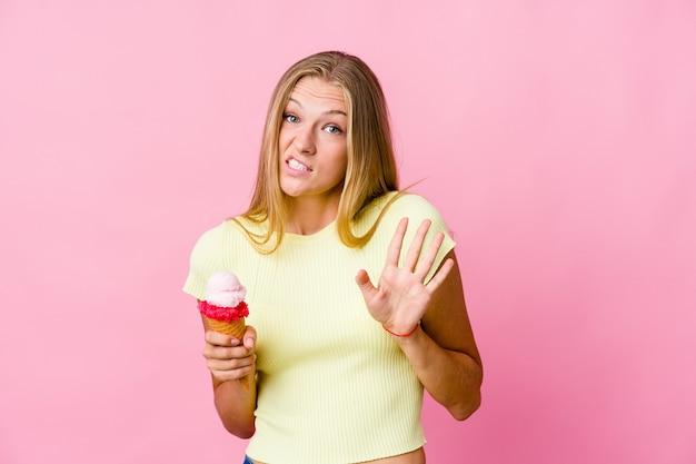 Jonge russische vrouw die een geïsoleerde roomijs eet die iemand verwerpt die een gebaar van walging toont