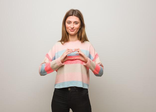 Jonge russische vrouw die een hartvorm met handen doet