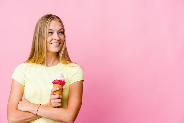 Jonge russische vrouw die een ijsje eet geïsoleerd glimlachend zelfverzekerd met gekruiste armen