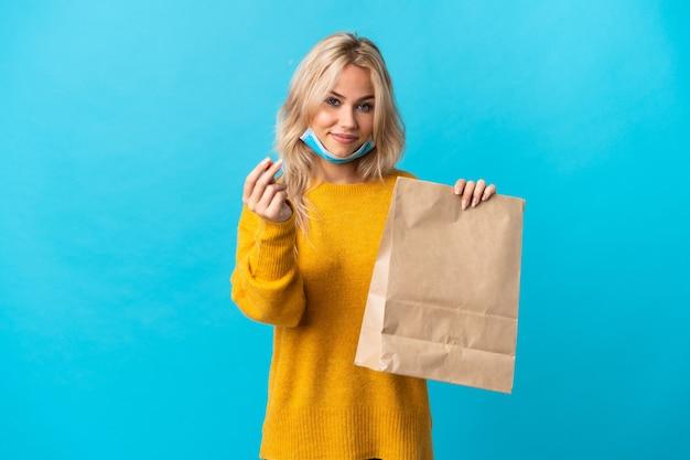 Jonge russische vrouw die een kruidenierswinkel het winkelen zak houdt die op blauwe muur wordt geïsoleerd die geldgebaar maakt