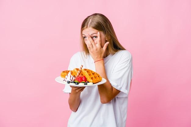 Jonge russische vrouw die een wafel eet, knippert door angstige en nerveuze vingers.