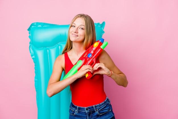 Jonge russische vrouw die met een waterpistool met een luchtbed speelt die en een hartvorm met handen glimlacht toont.