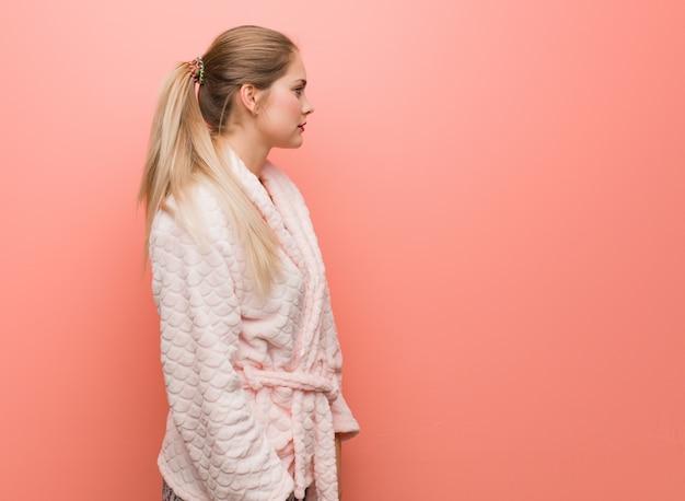 Jonge russische vrouw die pyjama aan de kant draagt die aan voorzijde kijkt