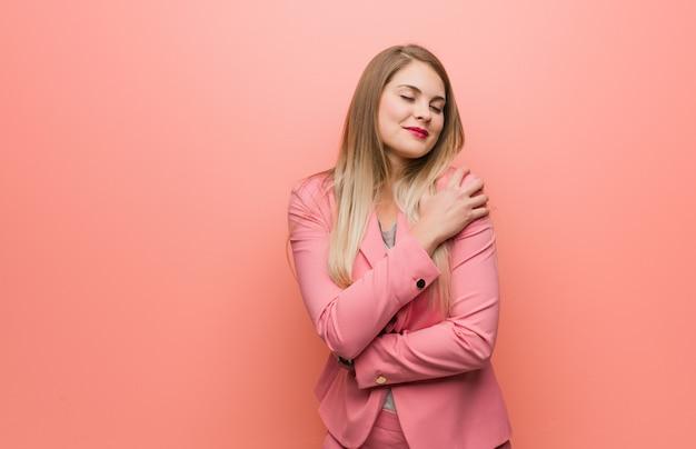 Jonge russische vrouw die pyjama draagt die een omhelzing geeft