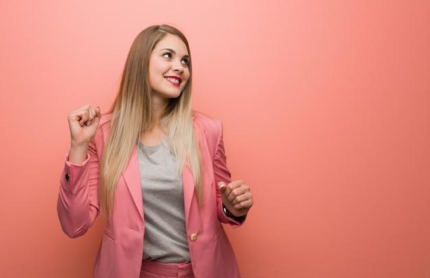 Jonge russische vrouw die pyjama draagt die en pret danst heeft