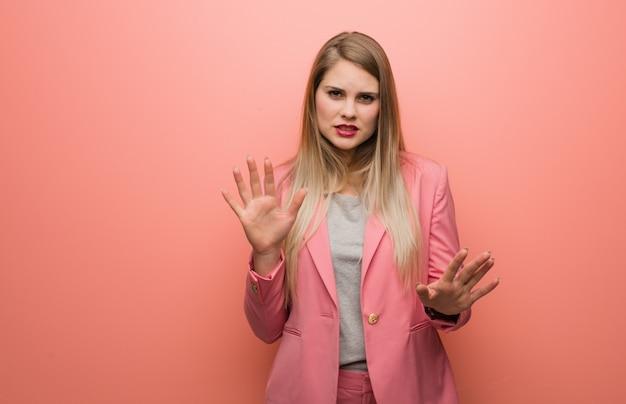Jonge russische vrouw die pyjama draagt die iets verwerpt dat een gebaar van afschuw doet