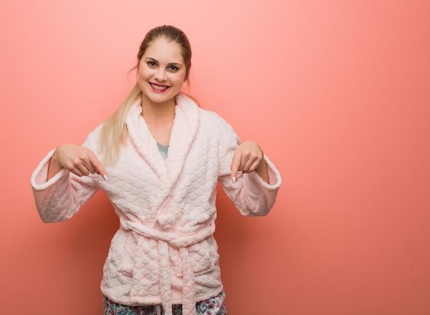 Jonge russische vrouw die pyjama draagt die naar de bodem met vingers richt